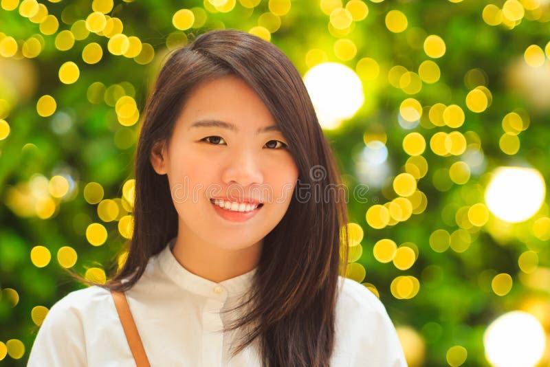 Vrij Aziatisch vrouwen binnenportret met Kerstmis Lichte achtergrond royalty-vrije stock afbeelding