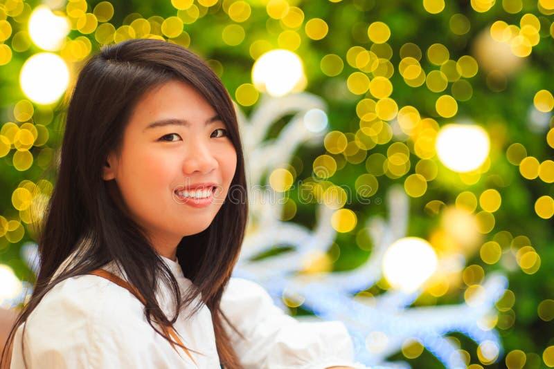 Vrij Aziatisch vrouwen binnenportret met Kerstmis Lichte achtergrond royalty-vrije stock afbeeldingen