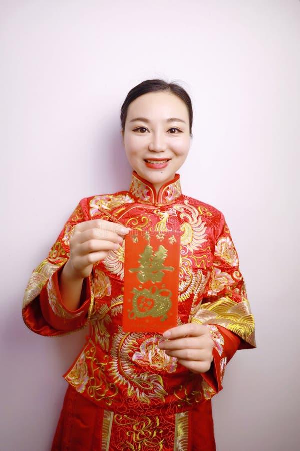 Vrij Aziatische Chinese mooie glimlachbruid met de Traditionele Chinese hand van de huwelijks rode kleding met rode document zak  stock afbeeldingen