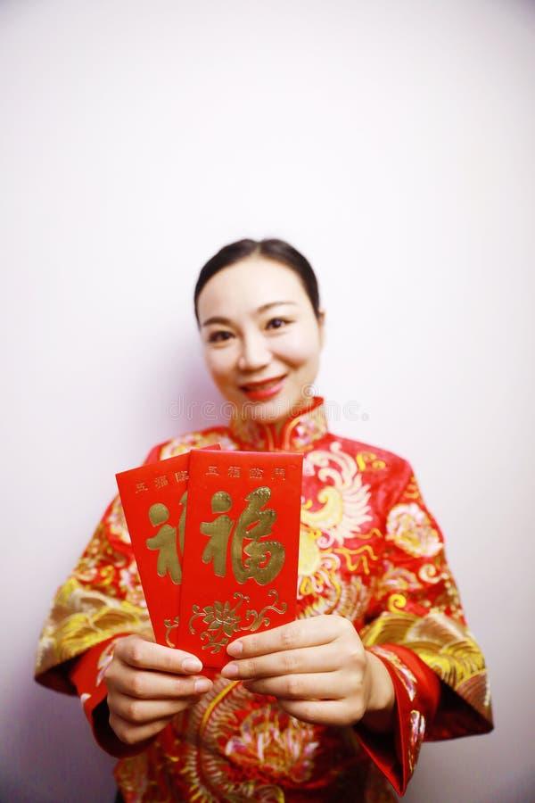 Vrij Aziatische Chinese mooie glimlachbruid met de Traditionele Chinese hand van de huwelijks rode kleding met rode document zak  royalty-vrije stock fotografie