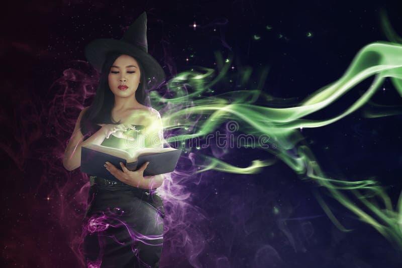Vrij Aziatische heksenvrouw die de bezweringsformule in boek lezen royalty-vrije stock fotografie