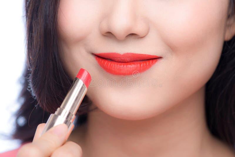 Vrij Aziatische jonge vrouw die rode matte lippenstift op haar lippen toepassen royalty-vrije stock afbeelding