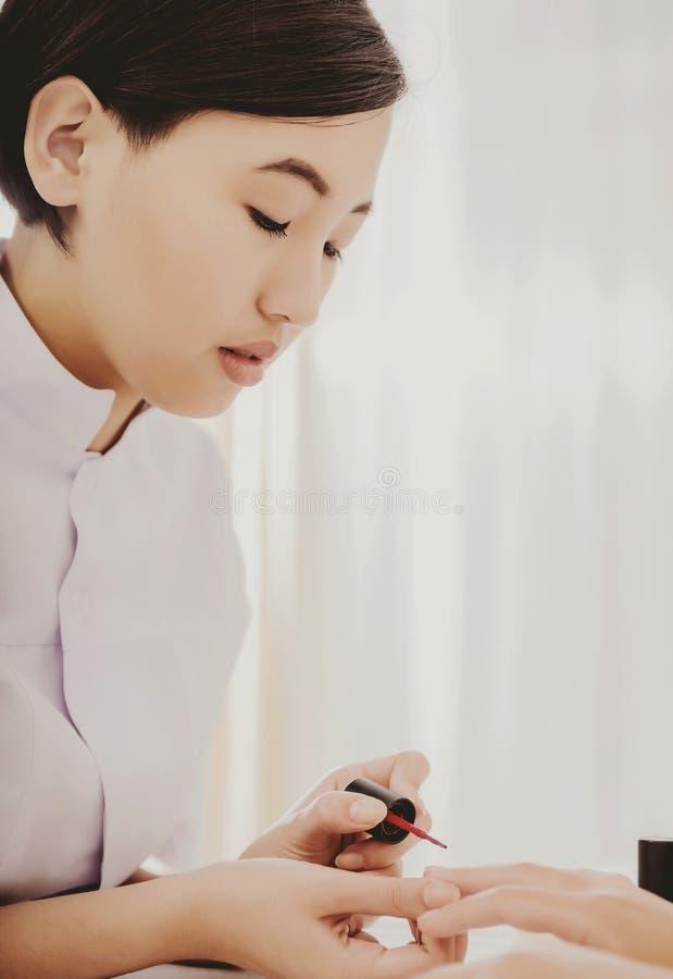 Vrij Aziatische manicure die nagellak toepassen royalty-vrije stock afbeeldingen