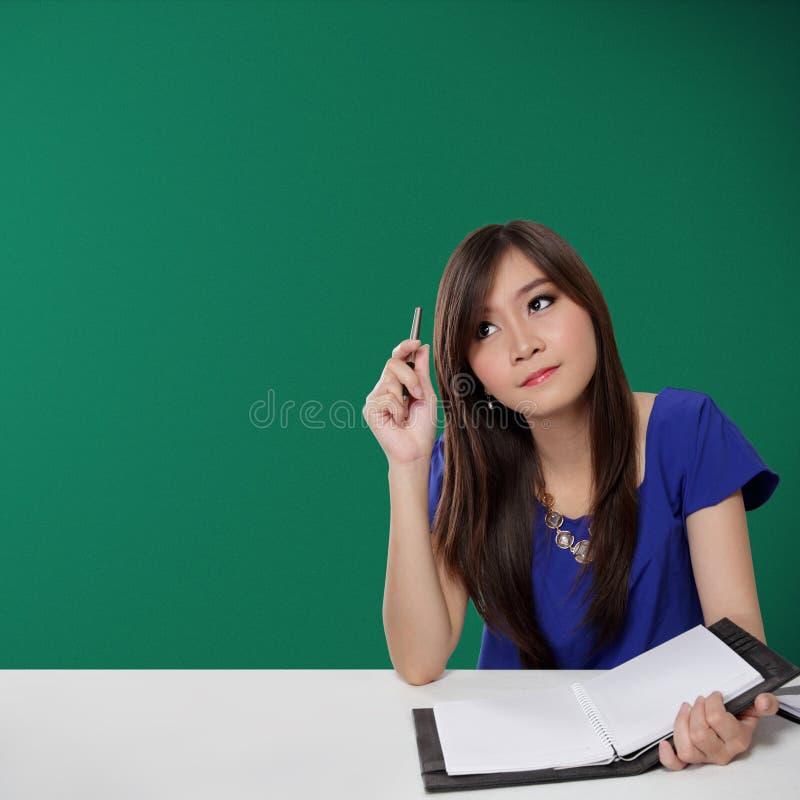 Vrij Aziatische student die omhoog voor inspiratie, op groene achtergrond kijken stock afbeelding