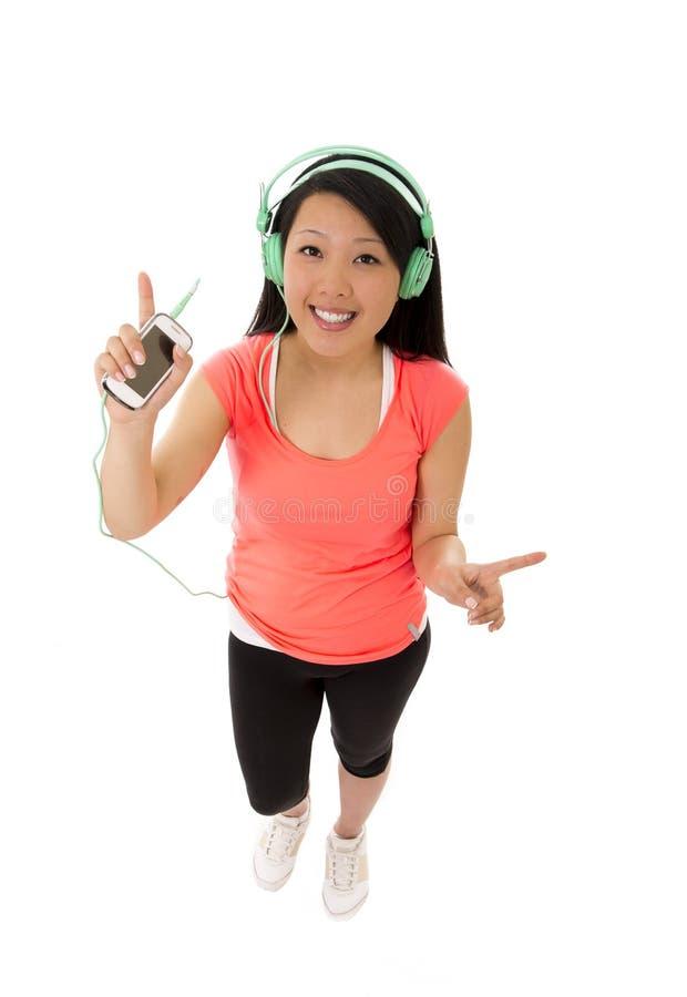 Vrij Aziatische vrouw die aan muziekhoofdtelefoons luisteren royalty-vrije stock afbeelding