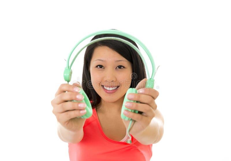 Vrij Aziatische vrouw die aan muziekhoofdtelefoons luisteren stock afbeelding