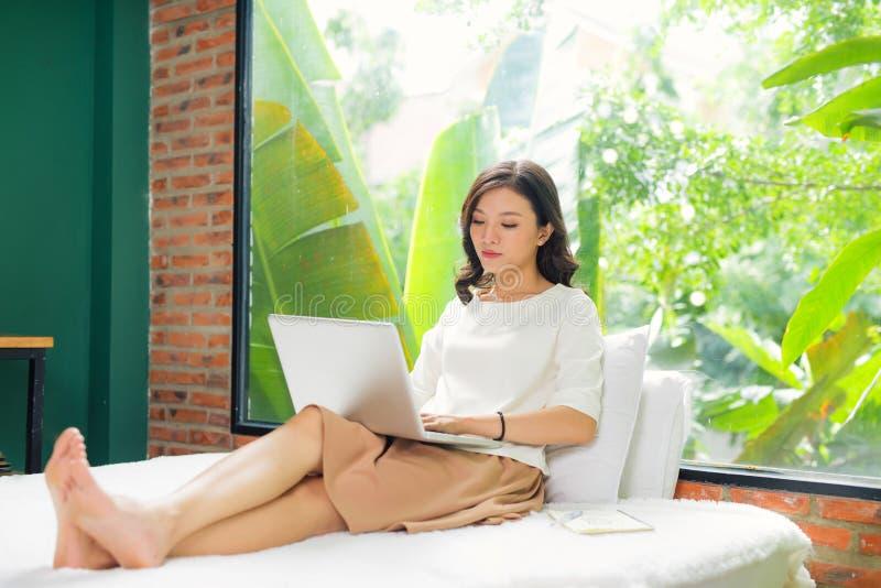 Vrij Aziatische vrouw die laptop computer in bed in ruimte met behulp van en smil stock foto