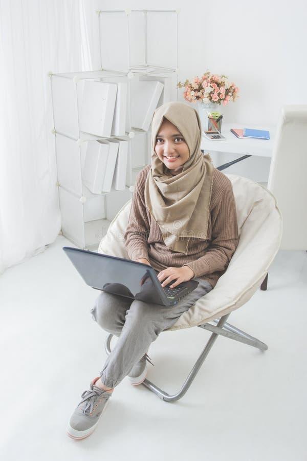 Vrij Aziatische vrouw die laptop thuis met behulp van royalty-vrije stock foto