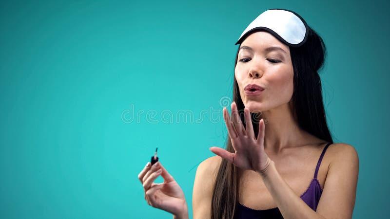 Vrij Aziatische vrouw die op nagellak blazen, die pyjama's en blinddoek, zorg dragen stock fotografie