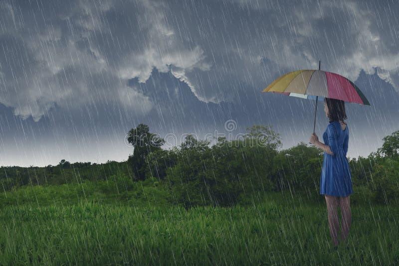 Vrij Aziatische vrouw die paraplu gebruiken wanneer regen royalty-vrije stock afbeeldingen