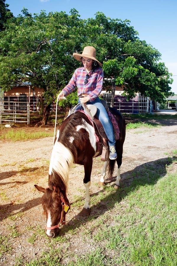 Vrij Aziatische vrouwenveedrijfster die een paard in openlucht in een landbouwbedrijf berijden royalty-vrije stock foto's