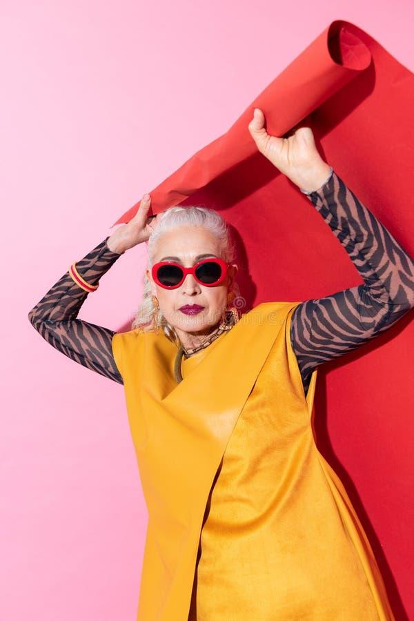 Vrij bejaard blondemodel die beide handen opheffen stock afbeeldingen