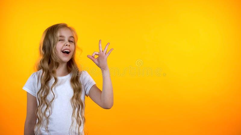 Vrij blond tienermeisje met krullend o.k. teken tonen en haar die, malplaatje knipogen royalty-vrije stock foto's