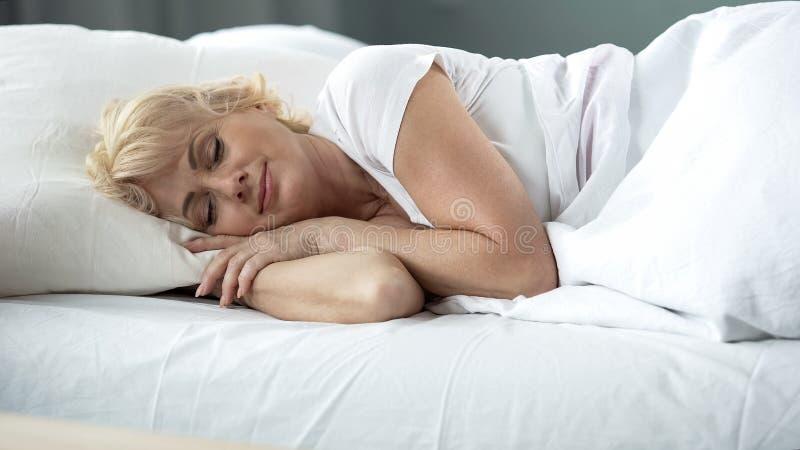 Vrij blonde dameslaap in bed, rust op comfortabele matras en hoofdkussen royalty-vrije stock foto