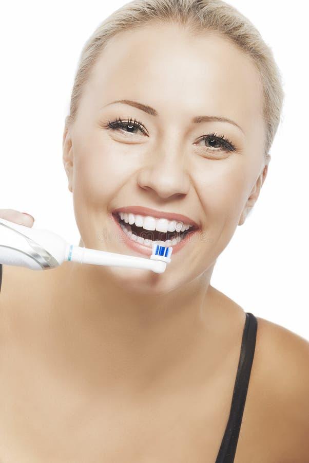 Vrij Blonde Glimlachende vrouw die Haar Tanden met Moderne Electr schoonmaken stock afbeeldingen
