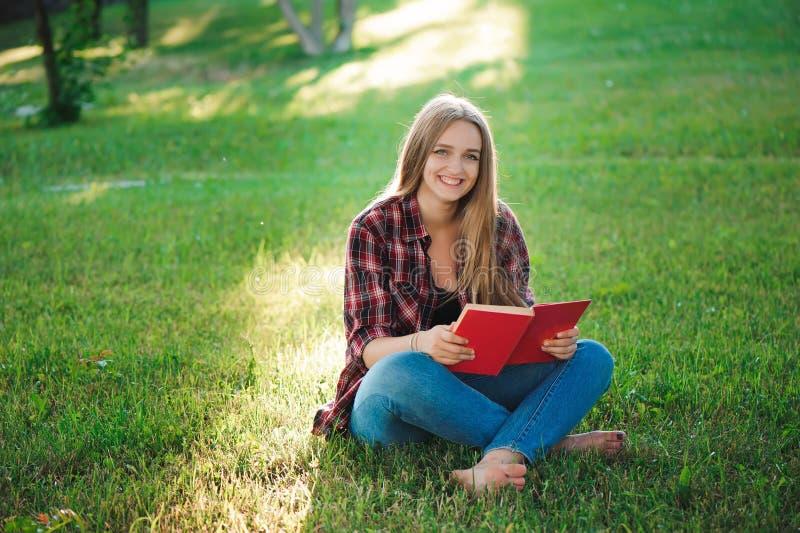 Vrij blonde jonge vrouw die een boek lezen bij park royalty-vrije stock fotografie