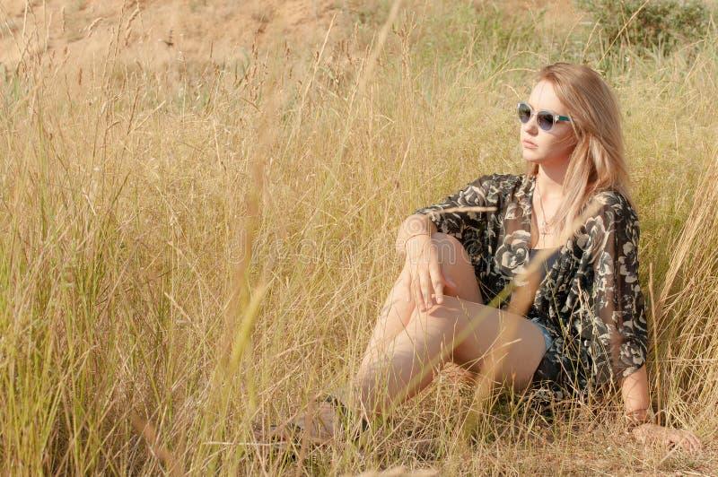 Vrij blonde meisjeszitting op gebied met droog gras royalty-vrije stock fotografie