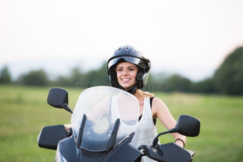 Vrij blonde vrouw die van een motorrit in platteland genieten stock afbeelding