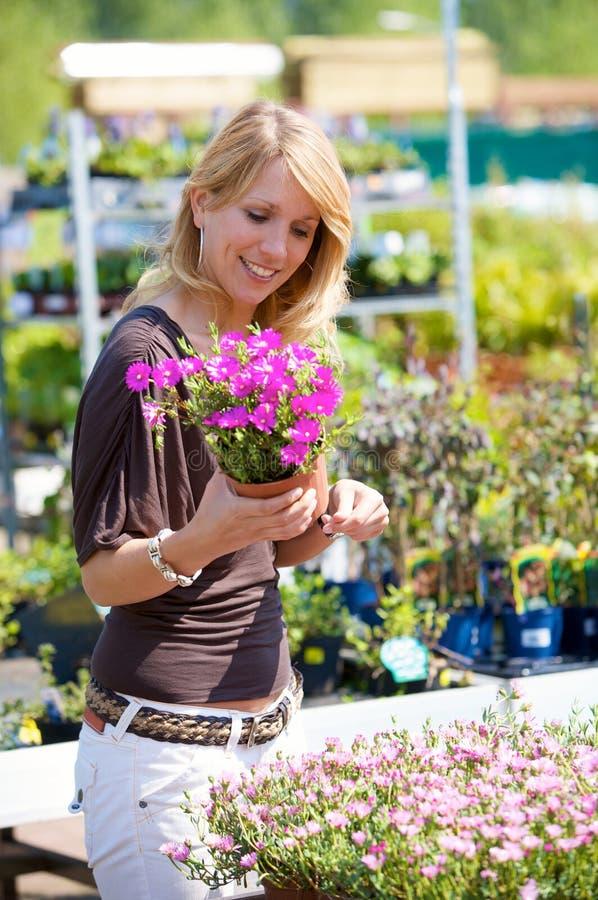 Vrij blonde vrouw in tuinierend centrum stock afbeeldingen