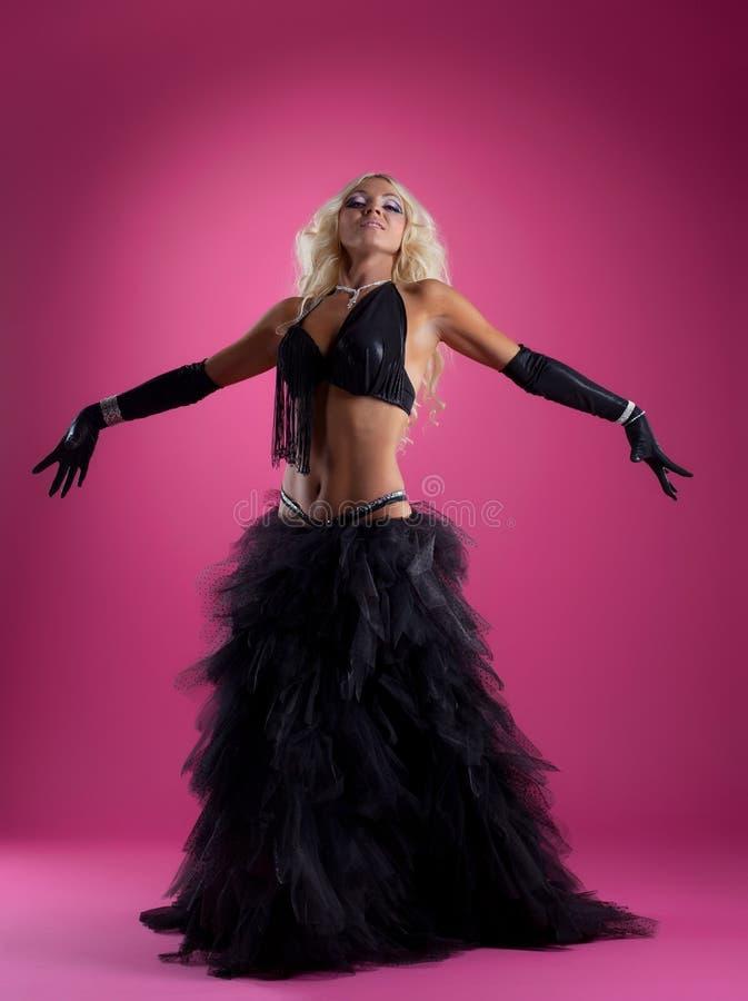 Vrij blonde vrouwendans in zwart Arabisch kostuum stock afbeeldingen