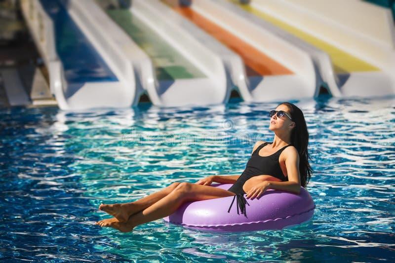 Vrij donkerbruine vrouw in bikini in het zwembad royalty-vrije stock foto