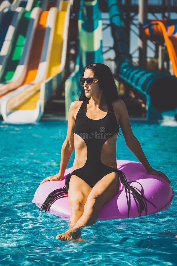 Vrij donkerbruine vrouw in bikini op de opblaasbare ring stock foto