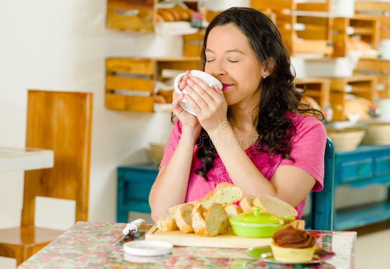 Vrij donkerbruine vrouwenzitting bij lijst binnen bakkerij, holdingskop van koffie en binnen gelukkig het glimlachen, broodselect stock fotografie