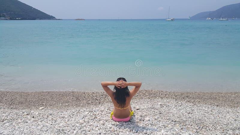 Vrij donkerbruine zitting op het strand royalty-vrije stock fotografie