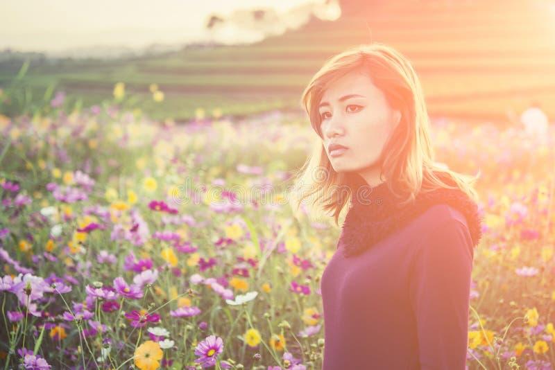 Vrij droevige jonge vrouw die iemand in bloemtuin wachten royalty-vrije stock foto's