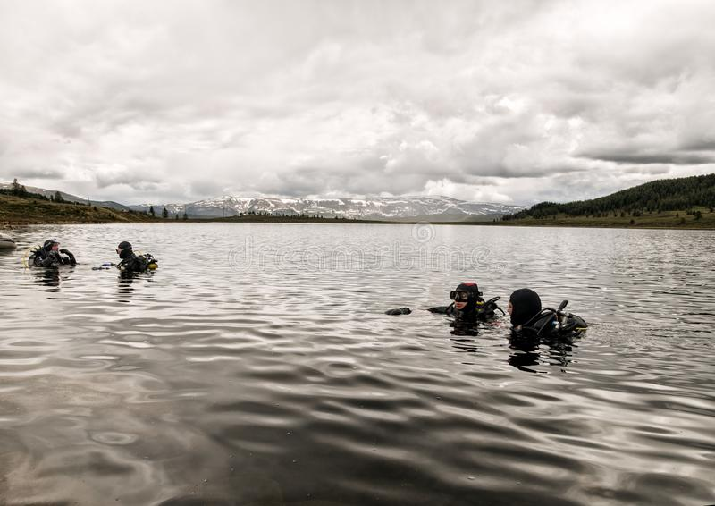 Vrij duiken in een bergmeer, het praktizeren technieken voor noodsituatieredders onderdompeling in koud water stock afbeelding