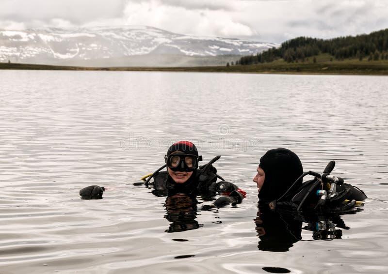 Vrij duiken in een bergmeer, het praktizeren technieken voor noodsituatieredders onderdompeling in koud water stock afbeeldingen
