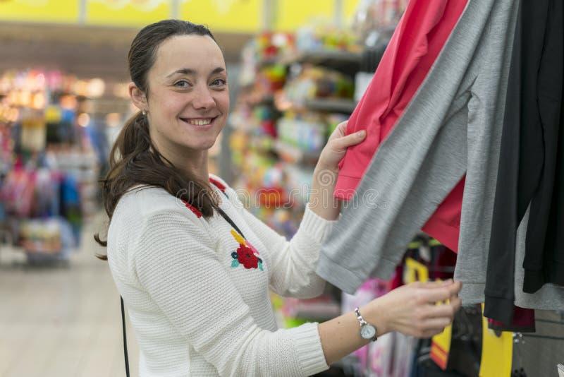 Vrij elegante vrouw die in klerenopslag winkelen De gelukkige vrouw kiest kleren stock afbeelding