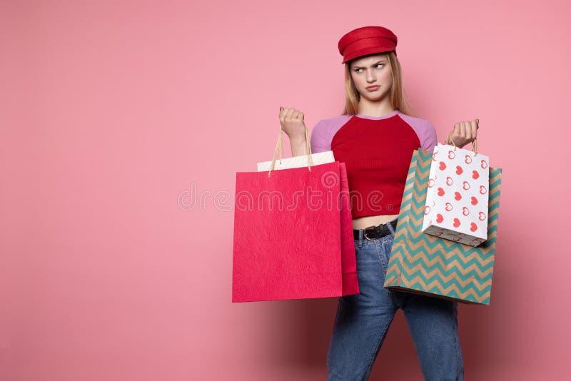 Vrij ernstig jong vrouwelijk model in modieuze rode hoed die zich tegen roze muur bevinden stock fotografie