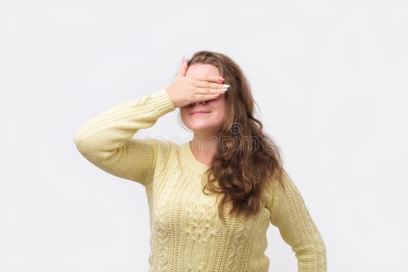 Vrij Europees meisje in gele sweater die haar ogen met hand sluiten, die gelukkige uitdrukking hebben royalty-vrije stock foto's