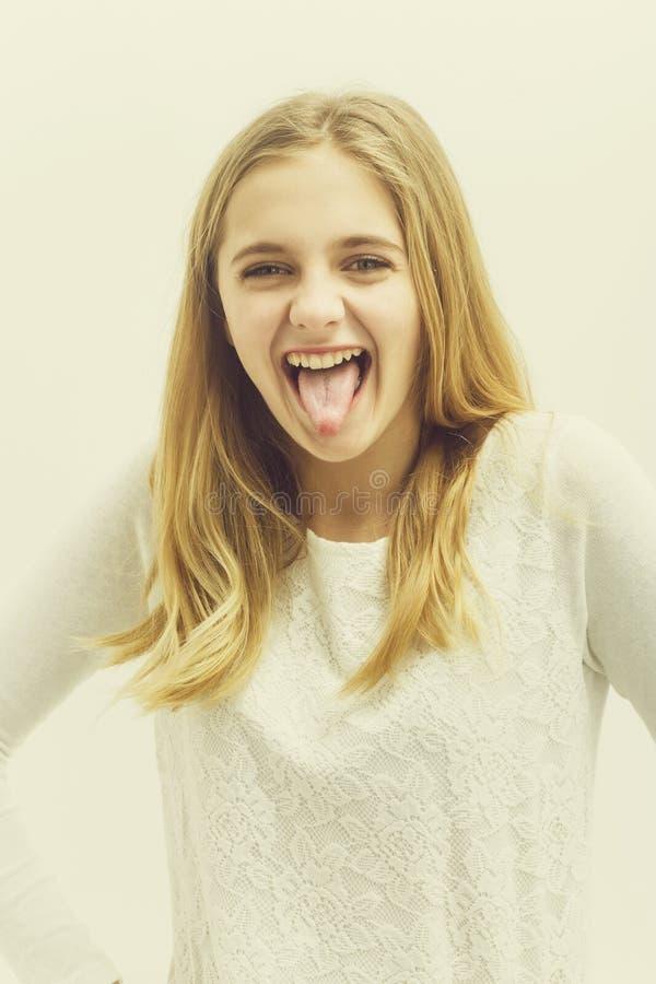 Vrij gelukkig jong meisje met blond haar die tong tonen royalty-vrije stock foto's
