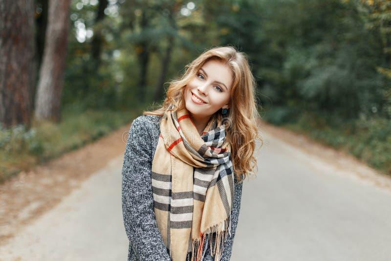 Vrij gelukkige jonge vrouw met een modieus kapsel met een mooie glimlach in een de lente modieuze laag royalty-vrije stock fotografie