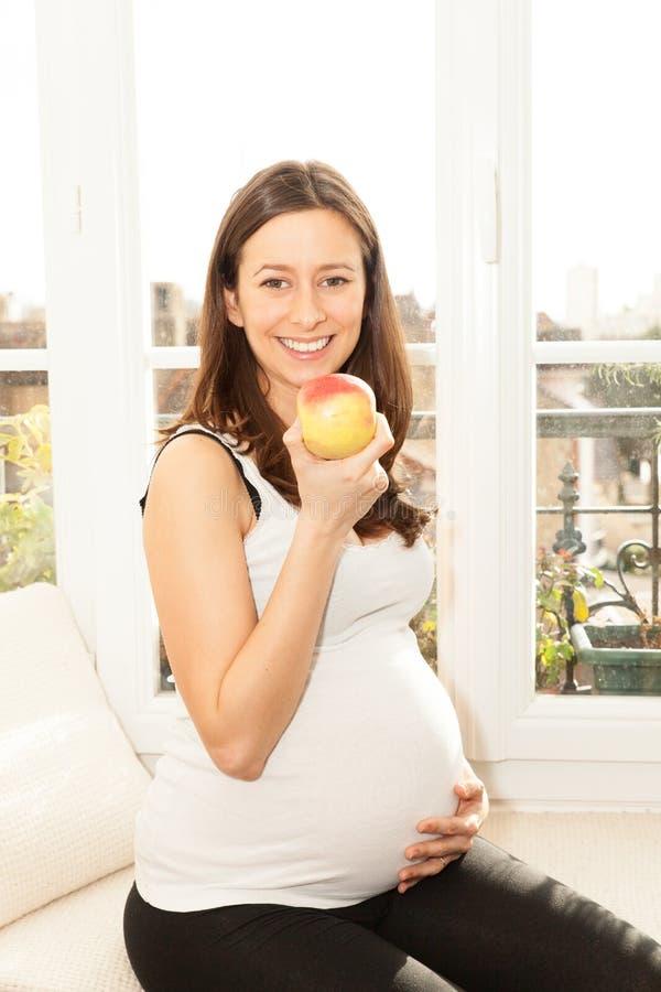 Vrij gelukkige jonge zwangere vrouw etend een appel royalty-vrije stock fotografie