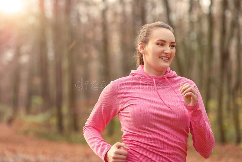 Vrij geschikte jonge vrouwenjogging in bos stock foto's