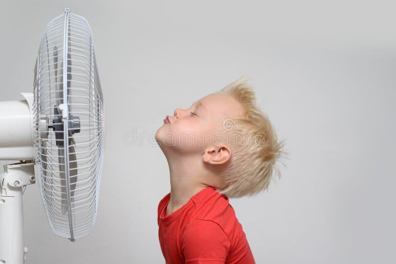 Vrij glimlachende blonde jongen die in rood overhemd en gesloten ogen van de koele lucht genieten Het concept van de zomer stock afbeelding