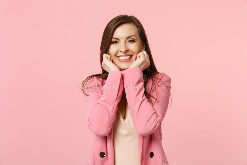 Vrij glimlachende charmante jonge vrouw die jasje dragen die holdingsvuisten dichtklemmen die dichtbij wangen op pastelkleur roze stock foto