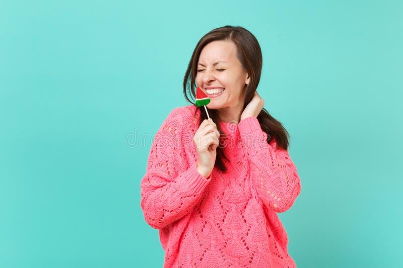 Vrij glimlachende jonge vrouw die in die gebreide roze sweater met gesloten ogen in hand watermeloenlolly houden op blauw wordt g royalty-vrije stock fotografie
