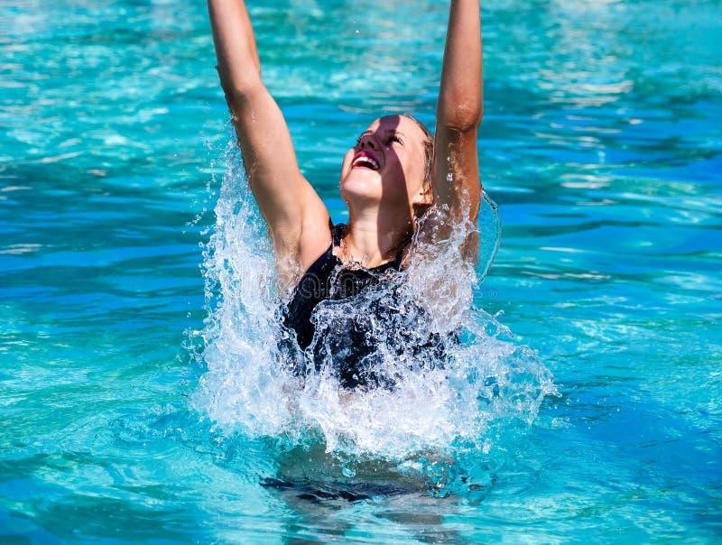 Vrij het atletische zon gelooide meisje bespatten in een zwembad op vakantie stock foto