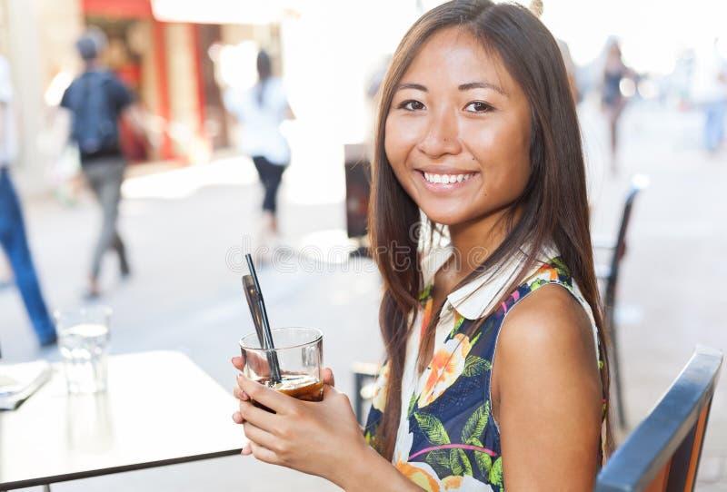 Vrij het Aziatische meisje drinken op terras royalty-vrije stock afbeelding