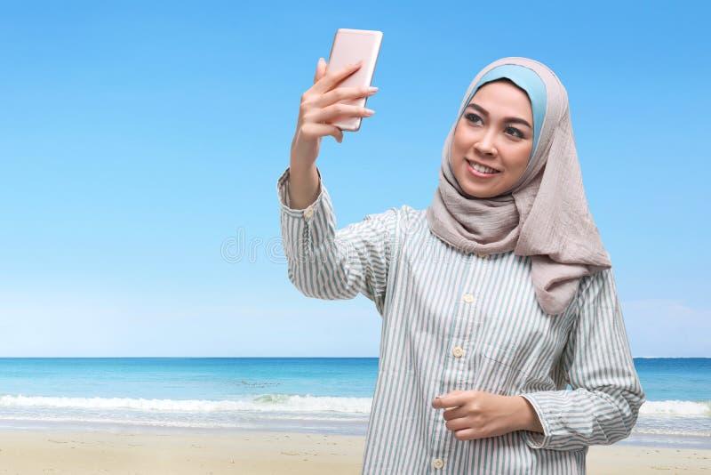 Vrij het Aziatische moslimvrouw stellende nemen selfie met mobiele telefoon royalty-vrije stock foto