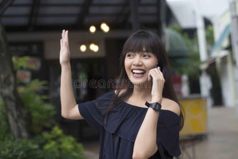 Vrij het Aziatische vrouw gelukkige spreken op cellphone en golft haar hand aan haar vriend royalty-vrije stock afbeeldingen