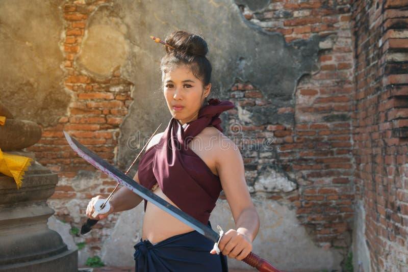 Vrij het Aziatische vrouw stellen in Thaise oude strijderskleding stock afbeelding