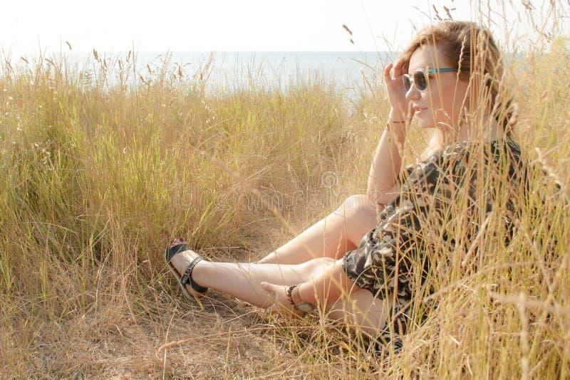 Vrij het blonde meisje ontspannen op gebied met droog gras stock afbeelding