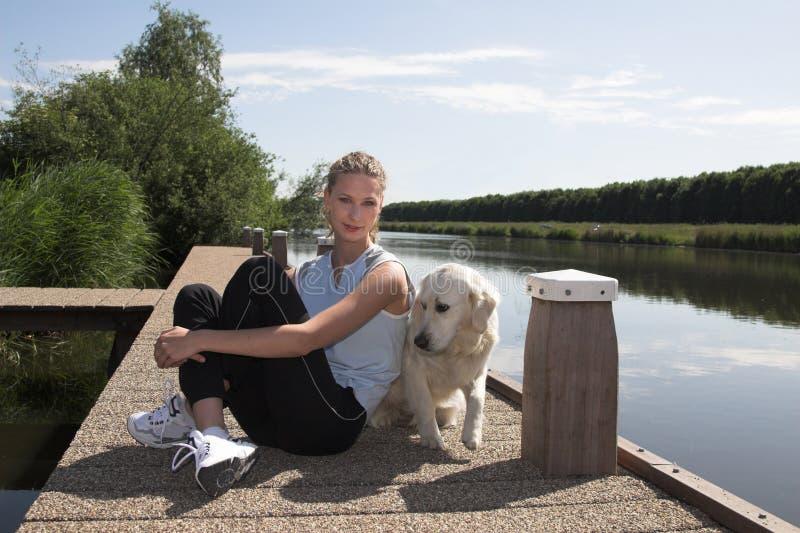 Vrij het blonde vrouw ontspannen met haar hond royalty-vrije stock fotografie