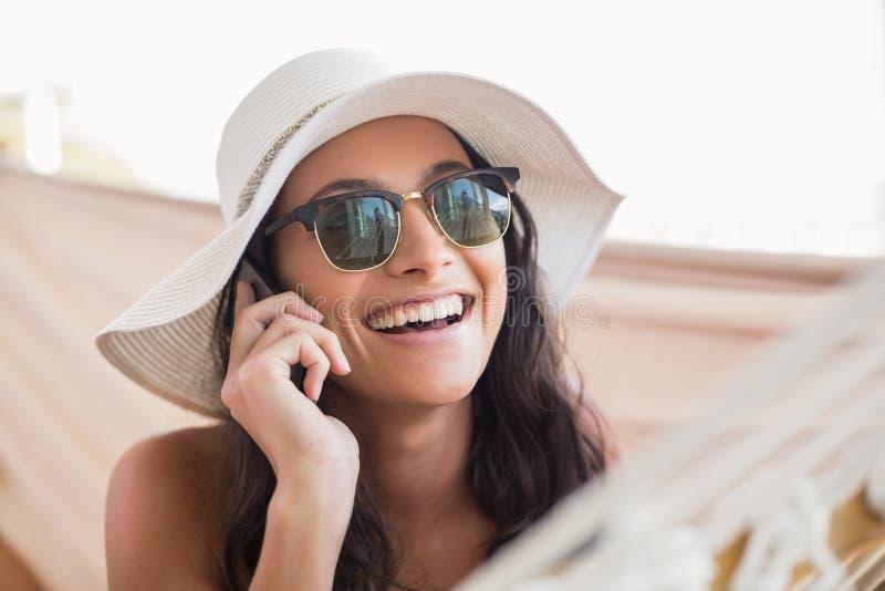 Vrij het donkerbruine ontspannen op een hangmat en het roepen met haar mobiele telefoon royalty-vrije stock afbeelding