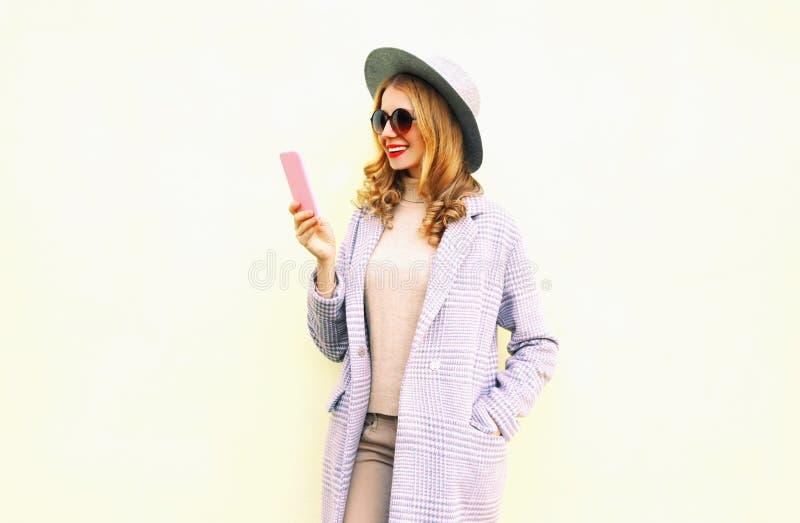 Vrij het glimlachen de jonge telefoon van de vrouwenholding met krullend haar in ronde hoed, roze laagjasje royalty-vrije stock foto